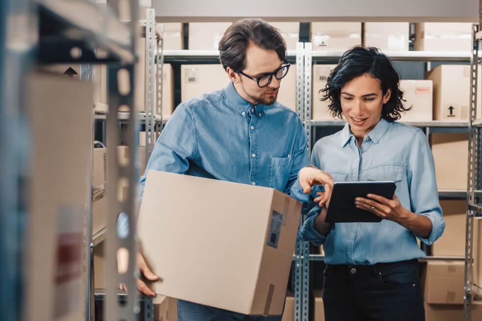 Ordenar trasteros grandes para guardar archivos de empresa - 2 personas consultando un inventario